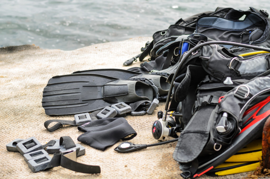 Pile of Scuba Diving Equipment Including Fins and Weights Drying on Coastal Dock near Water